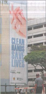 Huge hand hygiene poster on the wall of SGH in 2009. Image from: http://www.sgh.com.sg/about-us/newsroom/News-Articles-Reports/2009/Pages/sgh-steps-clean-hands-campaign-straits-times-thu-pg-b6.aspx