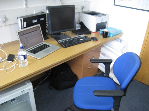 The desk space assigned to me at the Sanger Institute. Anyone opening the door too hard invariably knocked into the chair.